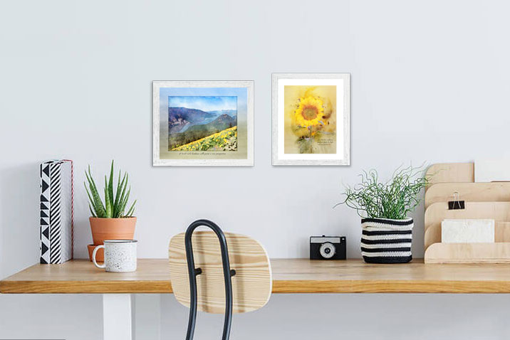 """Kindness Roots """"Art of Gratitude"""" Prints of a sunflower and river view are framed and displayed over a desk."""