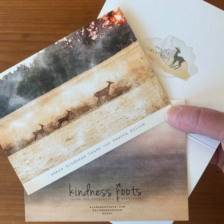 A gratitude card with a watercolor image of a family of deer walking through a hay field at sunset