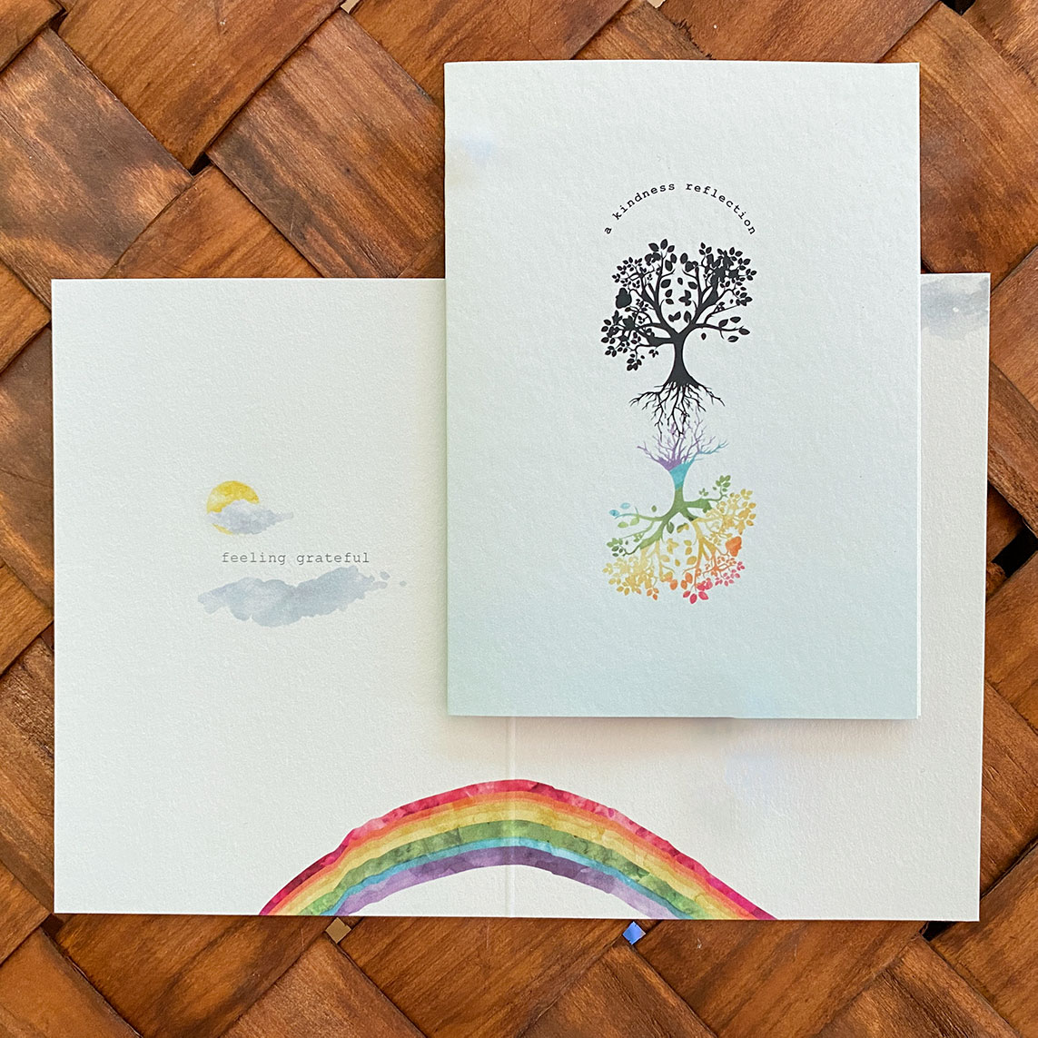 """A pastel blue gratitude card with a tree reflected in rainbow colors and quite """"a kindness reflection"""""""